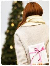 Девушка прячет новогодний подарок за спиной