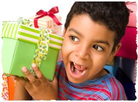 Ребенок радуется подарку в зелённой упаковке