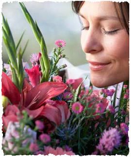 Женщина наслаждается ароматом подаренного букета цветов