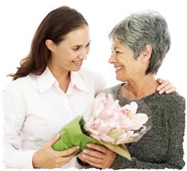 Дочь вручает букет цветов маме по случаю дня матери