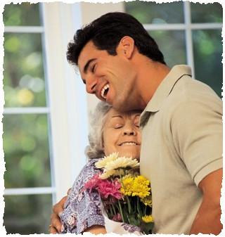 Взрослый сын поздравляет маму с праздником букетом цветов