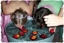 Девушки ловят яблоки из воды в бочке