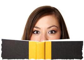 Читающая девушка выглядывает из-за книги
