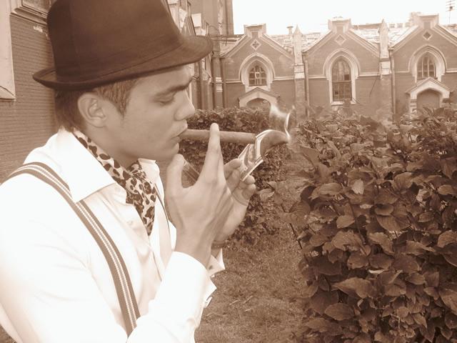Парень в костюме чикагского гангстера прикуривает сигару от банкноты