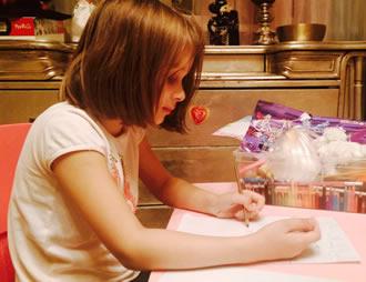 Девочка пишет письмо Деду Морозу с пожеланиями