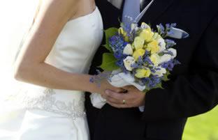 Молодые муж и жена держат свадебный букет